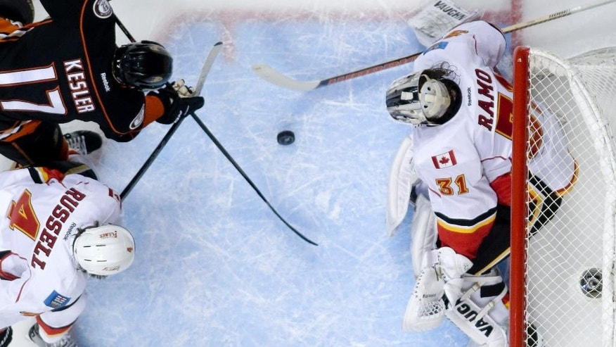 Calgary Flames goalie Karri Ramo blocks a shot by Anaheim Ducks center Ryan Kesler with the help of Kris Russell during the first period of Game 5 in an NHL hockey second-round playoff series in Anaheim, Calif., Sunday, May 10, 2015. (AP Photo/Chris Carlson)