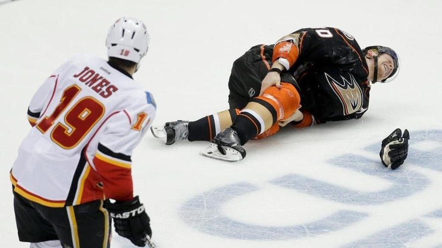 Anaheim Ducks right wing Corey Perry holds his knee after being checked as Calgary Flames right wing David Jones looks on during the second period of Game 5 in an NHL hockey second-round playoff series in Anaheim, Calif., Sunday, May 10, 2015. (AP Photo/Chris Carlson)