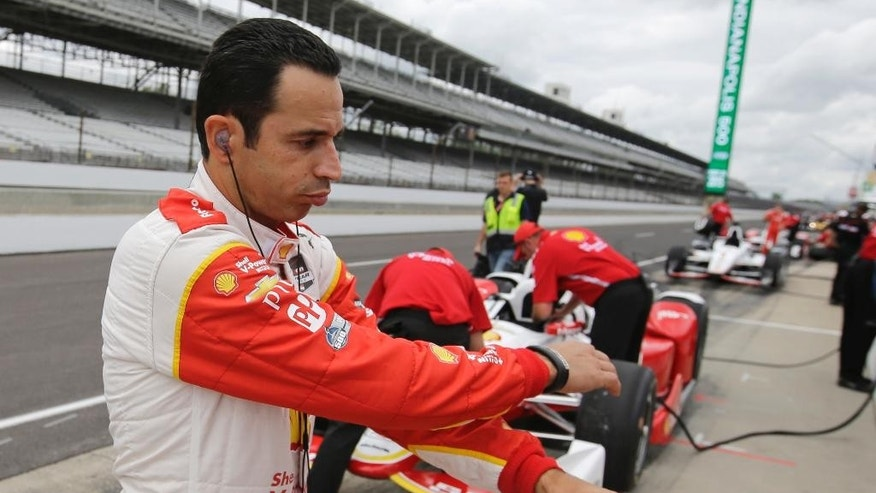 Helio Castroneves, of Brazil, stretches before a practice session for the Indianapolis 500 auto race at Indianapolis Motor Speedway in Indianapolis, Monday, May 11, 2015.  (AP Photo/Darron Cummings)