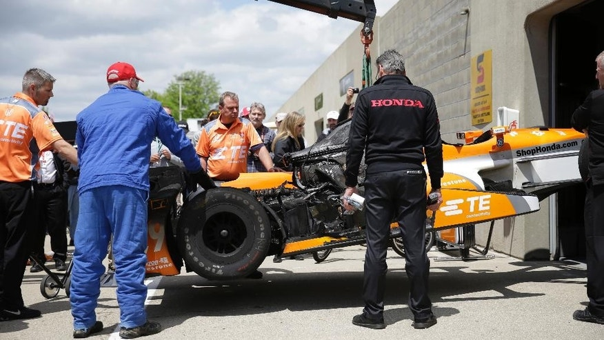 The car of Simona de Silvestro, of Switzerland, is lifted back to her garage after catching fire during practice for the Indianapolis 500 auto race at Indianapolis Motor Speedway in Indianapolis, Tuesday, May 12, 2015.  (AP Photo/AJ Mast)