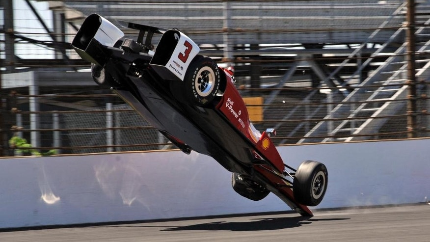 The car driven by Helio Castroneves, of Brazil, flips after hitting the wall in the first turn during practice for the Indianapolis 500 auto race at Indianapolis Motor Speedway in Indianapolis, Wednesday, May 13, 2015.  (AP Photo/Dick Darlington)