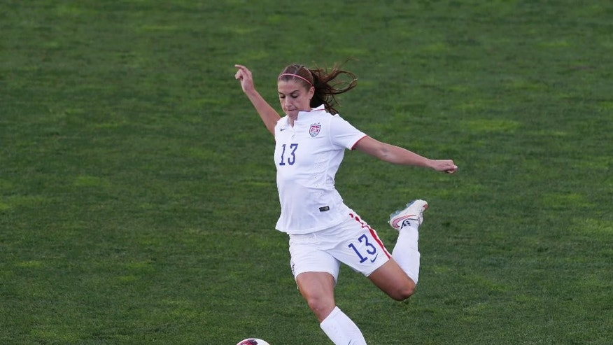 FILE - In this March 11, 2015, file photo, U.S. soccer player Alex Morgan shoots the ball during the women's soccer Algarve Cup final match against France at the Algarve stadium, outside Faro in southern Portugal. Morgan won't play when the team hosts Ireland Sunday, May 10, 2015, because of bone bruise in her left knee. Morgan will also miss an exhibition against Mexico next Sunday in Carson, California, because of the injury.  (AP Photo/Francisco Seco, File)