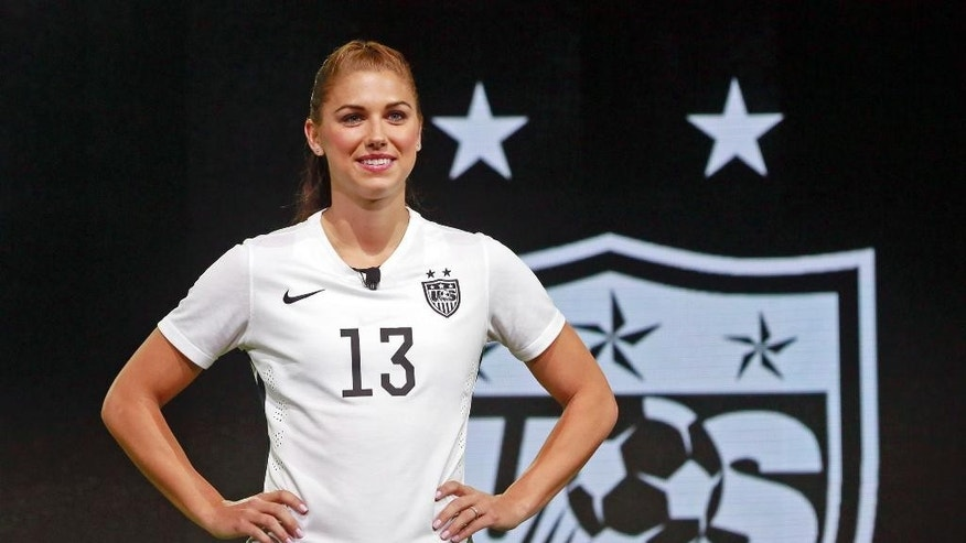 FILE - In this April 22, 2015, file photo, United States forward Alex Morgan poses in the new black and white home uniform for the U.S. women's World Cup soccer team during a news conference in Los Angeles. Morgan's star rose quickly following her performance in Germany four years ago, when - as the youngest player on the U.S. World Cup team - she became a super sub with a goal and an assist in the final match against Japan. Now she's a savvy veteran, handling her fame with aplomb as she prepares for her World Cup sequel. (AP Photo/Nick Ut, File)