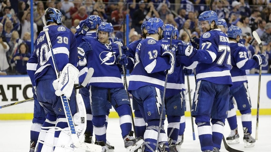 Members of the Tampa Bay Lightning celebrate after defeating the Montreal Canadiens 4-1 during Game 6 of a second-round NHL Stanley Cup hockey playoff series Tuesday, May 12, 2015, in Tampa, Fla. (AP Photo/Chris O'Meara)