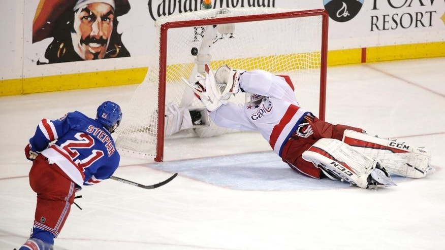 New York Rangers center Derek Stepan (21) shoots to score the game winning goal against Washington Capitals goalie Braden Holtby (70) during overtime of Game 7 of the Eastern Conference semifinals during the NHL hockey Stanley Cup playoffs Wednesday, May 13, 2015, in New York. The Rangers won 2-1. (AP Photo/Frank Franklin II)