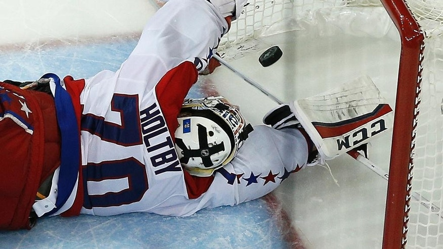 The puck, shot by New York Rangers center Derek Stepan (21) gets past Washington Capitals goalie Braden Holtby (70) for the winning goal in overtime of Game 7 of the Eastern Conference semifinals during the NHL hockey Stanley Cup playoffs, Wednesday, May 13, 2015, in New York. The Rangers won 2-1. (AP Photo/Julie Jacobson)