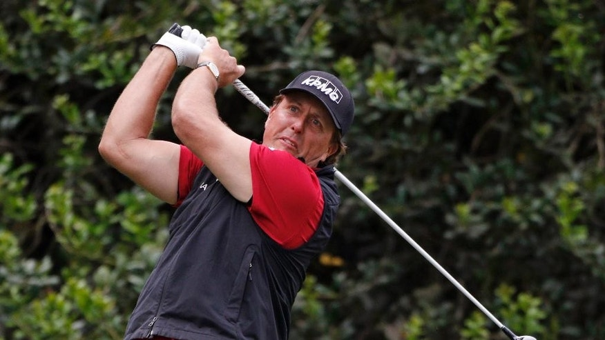 Phil Mickelson watches his tee shot on the 14th hole during the first round of the Wells Fargo Championship golf tournament at Quail Hollow Club in Charlotte, N.C., Thursday, May 14, 2015. (AP Photo/Bob Leverone)