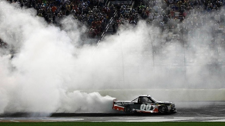 Kasey Kahne (00) does a burnout after winning the NASCAR Trucks series North Carolina Education Lottery auto race at Charlotte Motor Speedway in Concord, N.C., Friday, May 15, 2015. (AP Photo/Terry Renna)