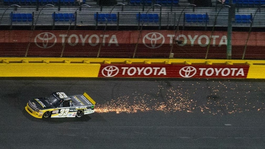 Sparks fly from the rear of Brandon Jones (33) truck as he prepares to enter Turn 4 during the NASCAR Trucks series auto race at Charlotte Motor Speedway in Concord, N.C., on Friday, May 15, 2015. (AP Photo/Chris Keane)