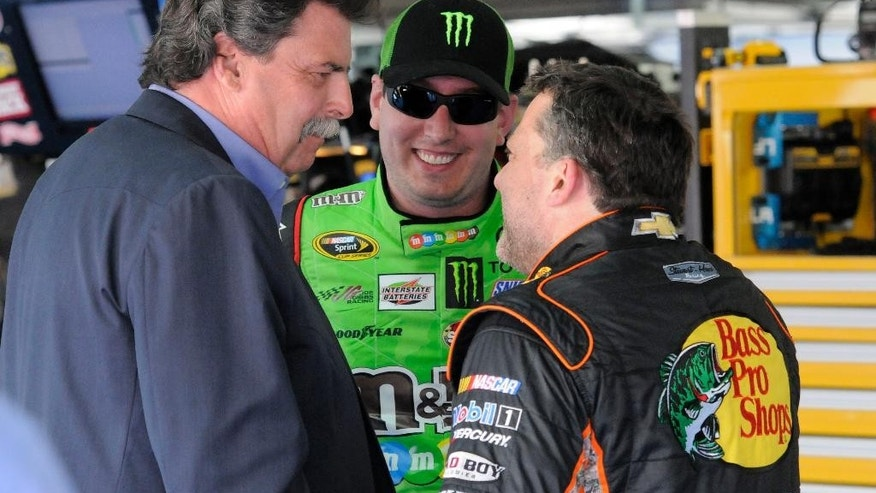 NASCAR Vice Chairman and Chief Operating Officer Mike Helton, left, speaks with Kyle Busch and Tony Stewart following practice for Saturday's NASCAR Sprint All-Star auto race in Concord, N.C., Friday, May 15, 2015. (AP Photo/Mike McCarn)