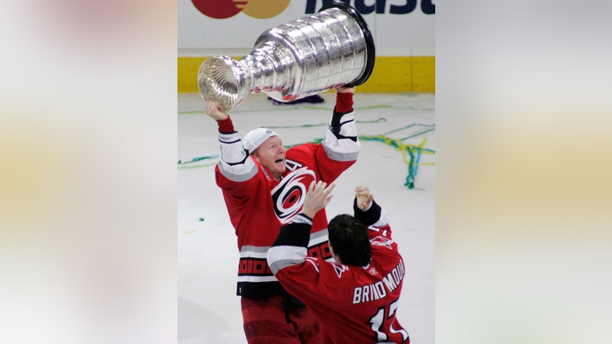 FILE - In this June 19, 2006, file photo, Carolina Hurricanes' Glen Wesley, left, receives the Stanley Cup from teammate Rod Brind'Amour after the Hurricanes defeated the Edmonton Oilers 3-1 in Game 7 of the Stanley Cup hockey finals in Raleigh, N.C.  The Washington Capitals and Tampa Bay Lightning, along with the Florida Panthers and Carolina Hurricanes, all have played in the Stanley Cup Finals, with Tampa Bay winning in 2004 and Carolina in 2006. (AP Photo/Karl DeBlaker, File)
