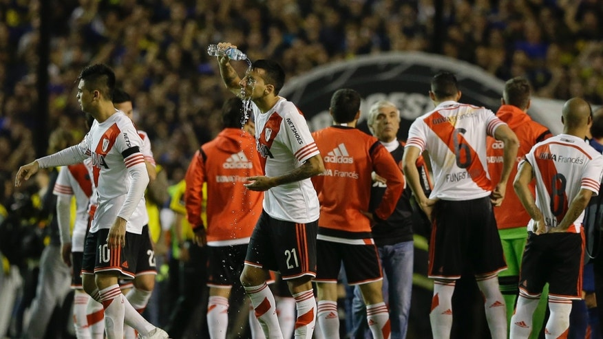 Argentina's River Plate players walk on the field as Leonel Vangioni rinses his face after pepper spray was thrown at them from the stands before the start of the first half of the Copa Libertadores round of sixteen soccer match against Boca Juniors in Buenos Aires, Argentina, Thursday, May 14, 2015. Conmebol authorities and referee Dario Herrera cancelled the game due to the incident. (AP Photo/Natacha Pisarenko)