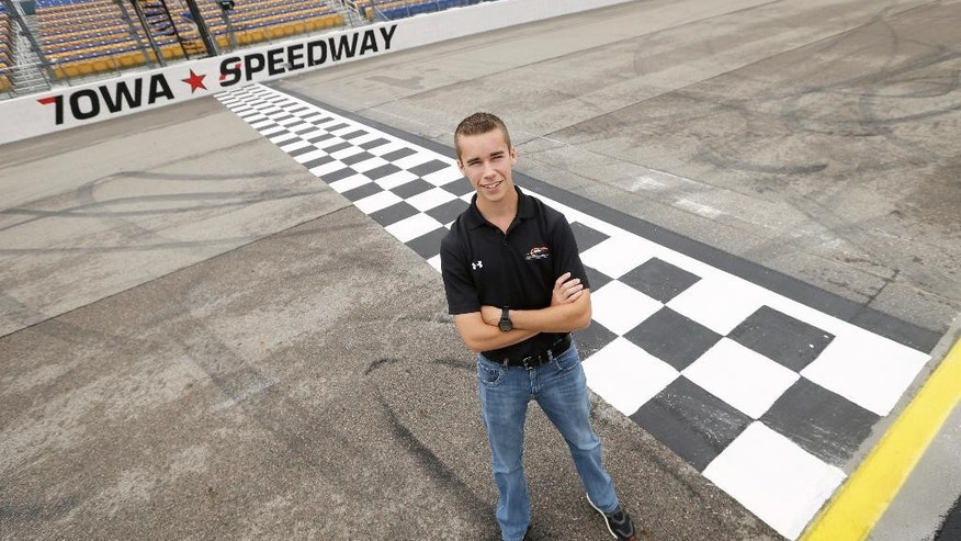 NASCAR xFinity driver Ben Rhodes stands on the finish line at Iowa Speedway, Friday, May 15, 2015, in Newton, Iowa. Rhodes is skipping his high school commencement so he can make his NASCAR xFinity debut Sunday at Iowa Speedway. (AP Photo/Charlie Neibergall)