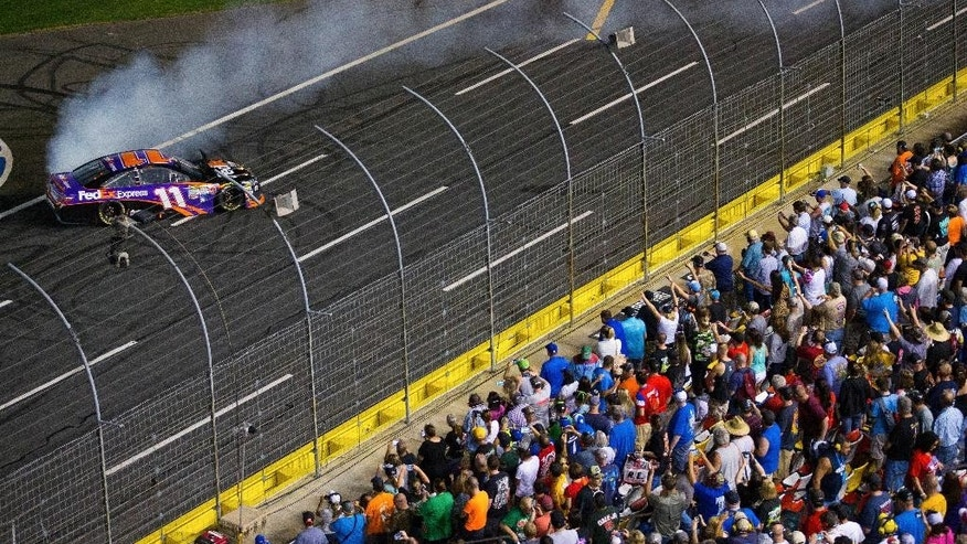 Denny Hamlin leaves a trail of smoke from a burnout after winning the NASCAR Sprint All-Star auto race at Charlotte Motor Speedway in Concord, N.C., on Saturday, May 16, 2015. (AP Photo/Chris Keane)