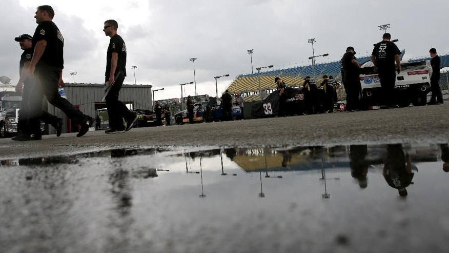 Rain falls as car line up for inspections before qualifying for the NASCAR Xfinity Series auto race at the Iowa Speedway, Saturday, May 16, 2015, in Newton, Iowa. (AP Photo/Justin Hayworth)