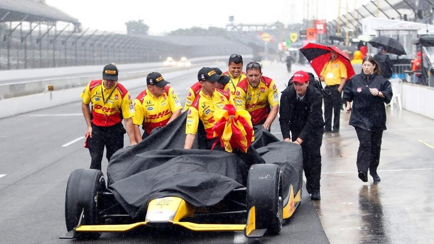 The crew of Ryan Hunter-Reay pushes the car back to the garage area after rain halted action on the first day of qualifications for the Indianapolis 500 auto race at Indianapolis Motor Speedway in Indianapolis, Saturday, May 16, 2015.  (AP Photo/AJ Mast)