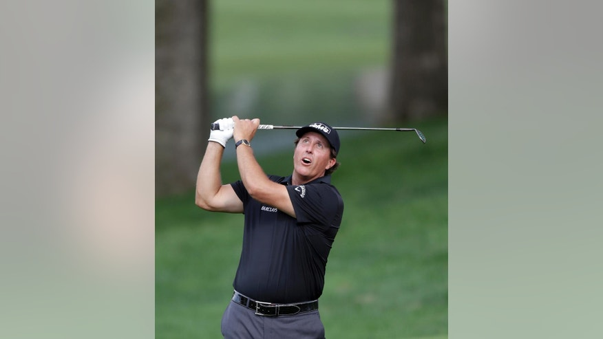 Phil Mickelson looks up toward the flight of the ball after a chip shot to the 15th green during the second round of the Wells Fargo Championship golf tournament at Quail Hollow Club in Charlotte, N.C., Friday, May 15, 2015. (AP Photo/Bob Leverone)