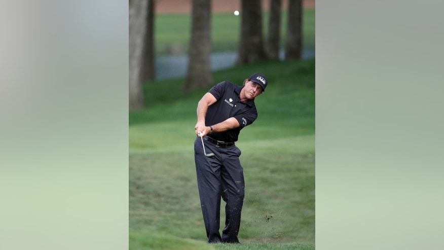 Phil Mickelson chips to the 15th hole during the second round of the Wells Fargo Championship golf tournament at Quail Hollow Club in Charlotte, N.C., Friday, May 15, 2015. (AP Photo/Chuck Burton)