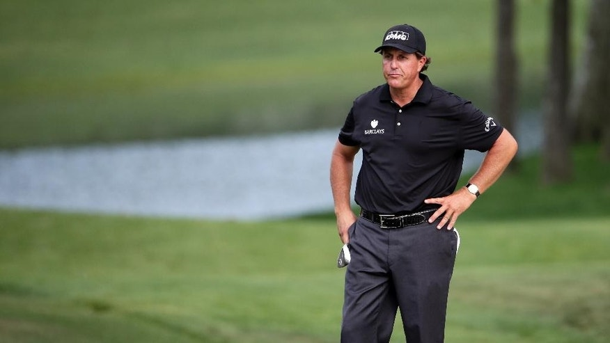 Phil Mickelson looks over his third shot on the 15th hole during the second round of the Wells Fargo Championship golf tournament at Quail Hollow Club in Charlotte, N.C., Friday, May 15, 2015. (AP Photo/Chuck Burton)