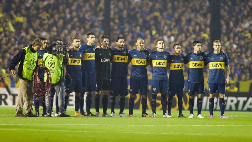 Argentina's Boca Juniors' players hold a minute of silence, in memory of an Argentine player who died earlier in the day, before a Copa Libertadores soccer match against River Plate in Buenos Aires, Argentina, Thursday, May 14, 2015. Emanuel Ortega, a 21-year-old fourth division soccer player, died after he was pushed by an opponent, and fell on concrete pillar during a fourth division game on May 3. Ortega died from his injury on Thursday. (AP Photo/Victor R. Caivano)
