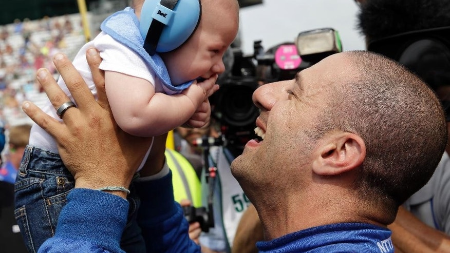 Tony Kanaan, of Brazil, picks up his son Deco after qualifying for the Indianapolis 500 auto race at Indianapolis Motor Speedway in Indianapolis, Sunday, May 17, 2015. (AP Photo/AJ Mast)