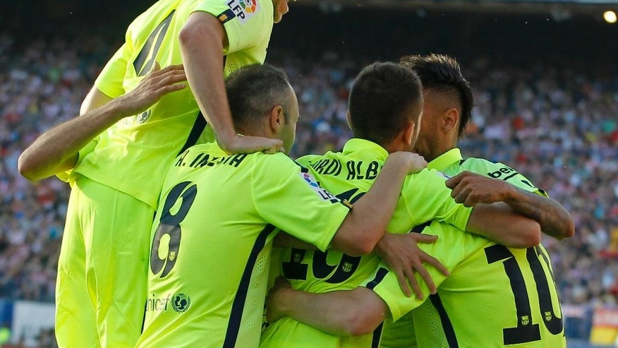 Barcelona players celebrate after Lionel Messi scored during a Spanish La Liga soccer match between Atletico Madrid and Barcelona at the Vicente Calderon stadium in Madrid, Spain, Sunday May 17, 2015. (AP Photo/Paul White)