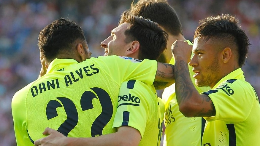 Barcelona's Lionel Messi, 2nd left, celebrates with team mates after scoring during a Spanish La Liga soccer match between Atletico Madrid and Barcelona at the Vicente Calderon stadium in Madrid, Spain, Sunday May 17, 2015. (AP Photo/Paul White)