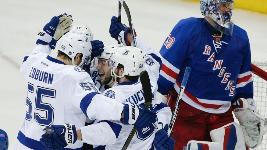 Tampa Bay Lightning center Tyler Johnson (9) is congratulated by teammates after scoring his third goal of the game against New York Rangers goalie Henrik Lundqvist (30) during the second period of Game 2 of the Eastern Conference final during the NHL hockey Stanley Cup playoffs, Monday, May 18, 2015, in New York. (AP Photo/Frank Franklin II)