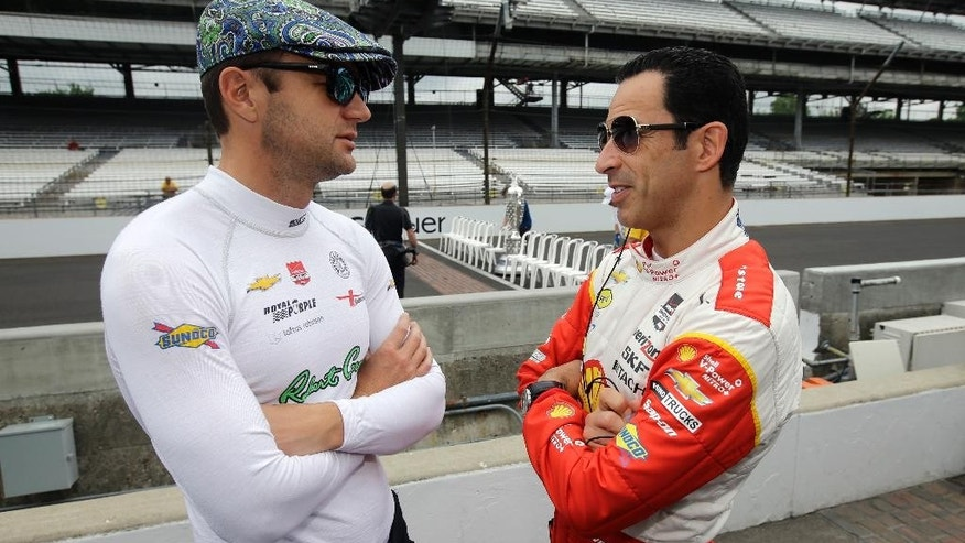 Helio Castroneves, of Brazil, right, talks with Townsend Bell before the start of practice for the Indianapolis 500 auto race at Indianapolis Motor Speedway in Indianapolis, Monday, May 18, 2015.  (AP Photo/Darron Cummings)
