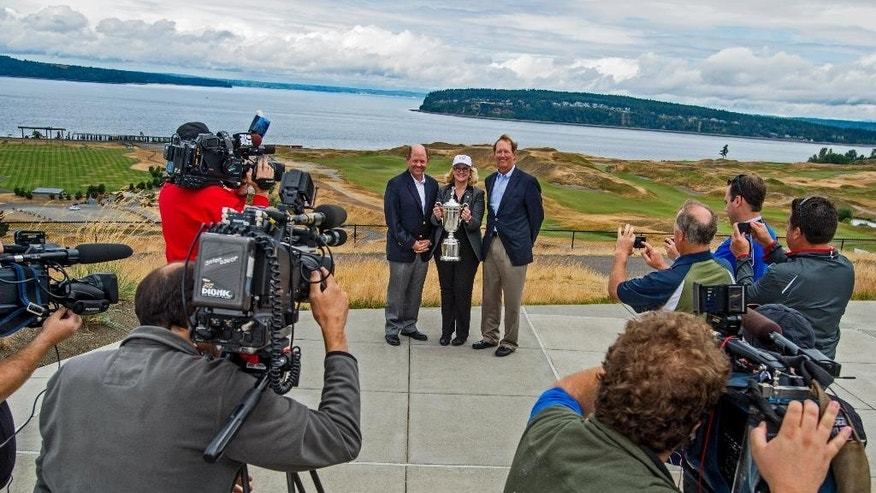 FILE - In this June 27, 2014, file photo, Mike Davis, left, executive director of U.S. Golf Association, Pierce County Executive Pat McCarthy, center, and USGA vice president Dan Burton pose with a U.S Open Championship trophy during a news conference at Chambers Bay Golf Course in University Place, Wash. Mike Davis hasn't caused this much consternation since he spoke to PGA Tour players about the evils on the long putter. Only this time, he was extolling the virtues of Chambers Bay. (AP Photo/The News Tribune, Peter Haley, File)