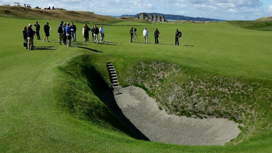FILE - In this Sept. 30, 2014, file photo, reporters and photographers stand near the deep pot bunker on the 18th fairway at Chambers Bay, the host course for the 2015 U.S. Open Championship, in University Place, Wash. Mike Davis hasn't caused this much consternation since he spoke to PGA Tour players about the evils on the long putter. Only this time, he was extolling the virtues of Chambers Bay. (AP Photo/Ted S. Warren, File)