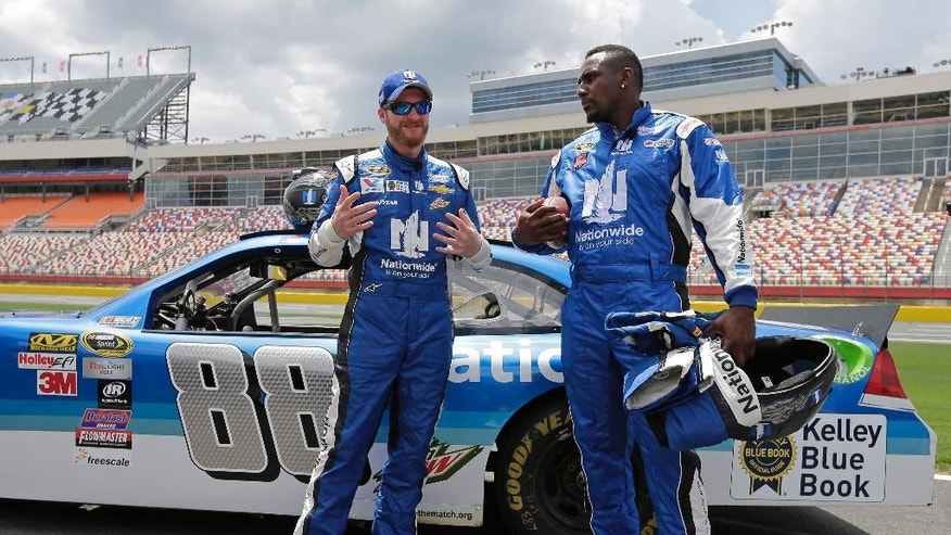Dale Earnhardt Jr., left, talks with Carolina Panthers linebacker Thomas Davis, right, during a news conference at Charlotte Motor Speedway in Concord, N.C., Tuesday, May 19, 2015. Davis, the NFL's Man of the Year, has been selected to be the honorary pace car driver for the Coca Cola 600 on Sunday. Dale Earnhardt Jr took Davis on several high speed laps around the track. (AP Photo/Chuck Burton)
