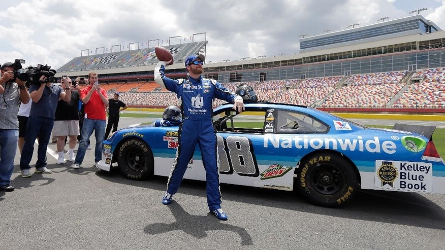 Dale Earnhardt Jr. throws a football to Carolina Panthers linebacker Thomas Davis during a news conference at Charlotte Motor Speedway in Concord, N.C., Tuesday, May 19, 2015. Davis, the NFL's Man of the Year, has been selected to be the honorary pace car driver for the Coca Cola 600 on Sunday. Dale Earnhardt Jr. took Davis on several high speed laps around the track. (AP Photo/Chuck Burton)