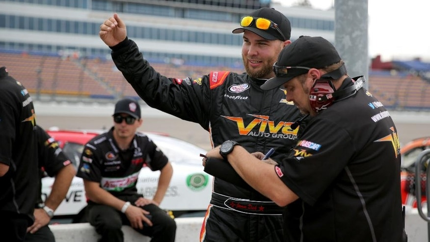 Jamie Dick talks with members of his crew after his first qualifying run for the NASCAR Xfinity Series auto race at the Iowa Speedway, Saturday, May 16, 2015, in Newton, Iowa.  During the end of the morning practice run Dick had a piece of lead from another car come through the windshield of his car and hit him in his helmet. (AP Photo/Justin Hayworth)