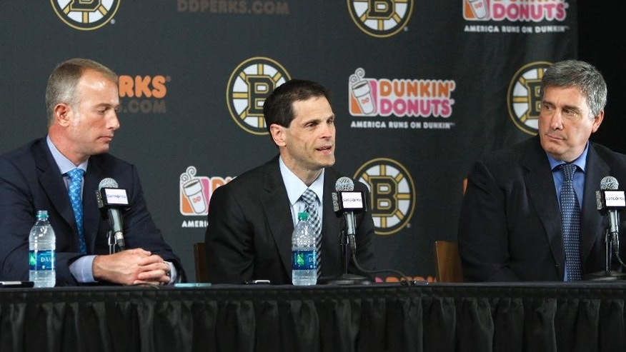 Boston Bruins general manager Don Sweeney, center, speaks between Charlie Jacobs, left, Chief Executive Officer of Delaware North's Boston holdings, which includes the Bruins, and Bruins president Cam Neely, right, after being introduced Wednesday, May 20, 2015, in Boston. Sweeney was elevated to general manager, taking over for his former boss, Peter Chiarelli, who was fired in April after the team missed the playoffs for the first time in eight years. (AP Photo/Bill Sikes)