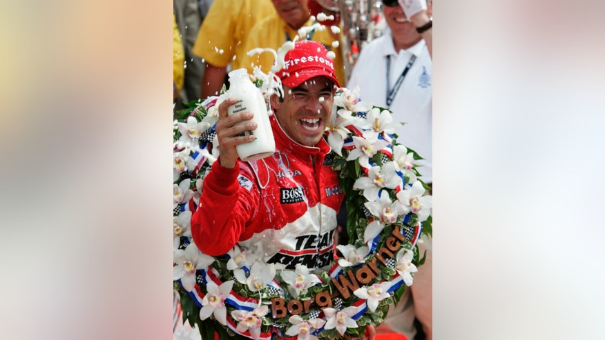 FILE - In this May 24, 2009, file photo, Helio Castroneves, of Brazil, douses himself with milk after winning the Indianapolis 500 auto race at Indianapolis Motor Speedway in Indianapolis. The specks of gray peeking out of Helio Castroneves' trademark jet black hair tell one side of his legacy. Yes, the Brazilian star is on the back end of his career. There's still one way he can always feel young: Scaling a fence and sipping the milk in Victory Lane. It never gets old. (AP Photo/Michael Conroy, File)