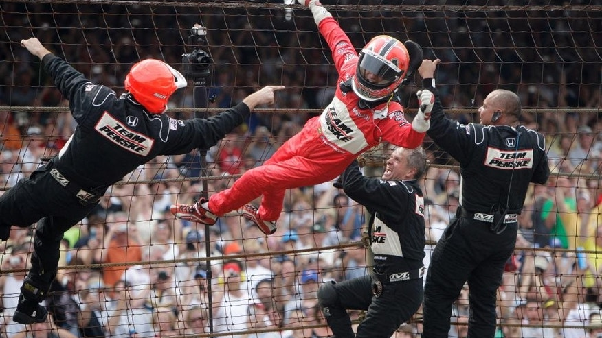 FILE - In this May 24, 2009, file photo, Helio Castroneves, of Brazil, climbs the safety fence with members of his pit crew after winning the Indianapolis 500 auto race at Indianapolis Motor Speedway in Indianapolis. The specks of gray peeking out of Castroneves' trademark jet black hair tell one side of his legacy. Yes, the Brazilian star is on the back end of his career. There's still one way he can always feel young: Scaling a fence and sipping the milk in Victory Lane. It never gets old. (AP Photo/Jeff Roberson, File)