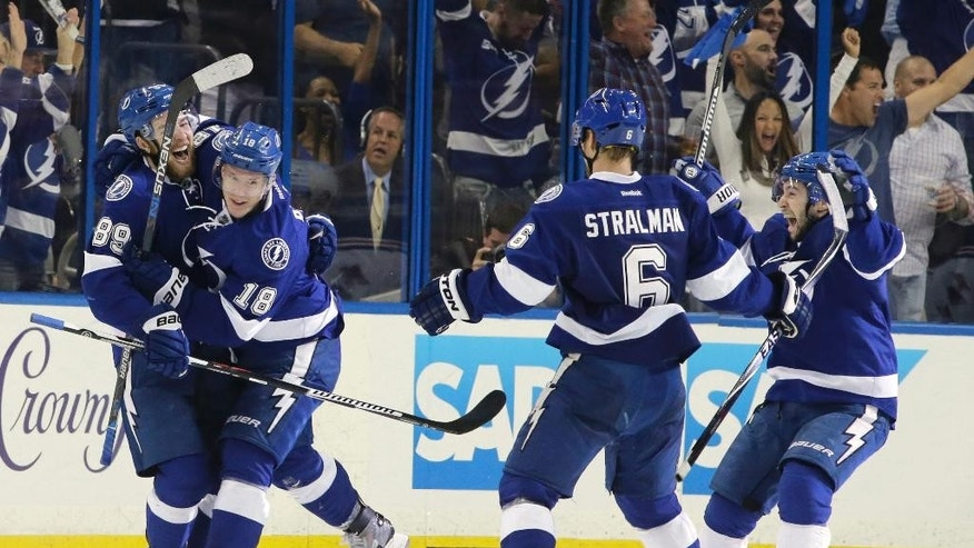 Tampa Bay Lightning left wing Ondrej Palat (18), of the Czech Republic, is congratulated by defensemd Nikita Nesterov (89), of Russia, and Anton Stralman (6), of Sweden, during the third period of Game 3 of the Eastern Conference finals against the New York Rangers in the NHL hockey Stanley Cup playoffs Wednesday, May 20, 2015, in Tampa, Fla. (AP Photo/Chris O'Meara)