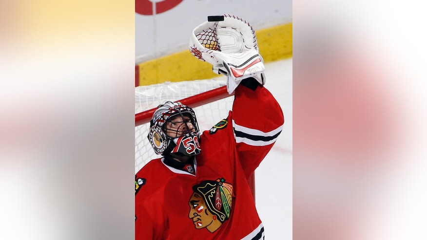 Chicago Blackhawks goalie Corey Crawford reaches for the puck during the second period in Game 3 of the Western Conference finals against the Anaheim Ducks in the NHL hockey Stanley Cup playoffs, Thursday, May 21, 2015, in Chicago. (AP Photo/Charles Rex Arbogast)