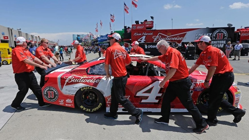 Crew members push driver Kevin Harvick's car through the garage before practice for Sunday's NASCAR Coca-Cola 600 Sprint Cup series auto race at Charlotte Motor Speedway in Concord, N.C., Thursday, May 21, 2015. (AP Photo/Chuck Burton)