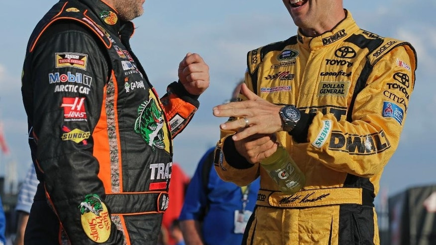 Matt Kenseth, right, talks with Tony Stewart before qualifying for Sunday's NASCAR Sprint Cup series auto race at Charlotte Motor Speedway in Concord, N.C., Thursday, May 21, 2015. (AP Photo/Chuck Burton)