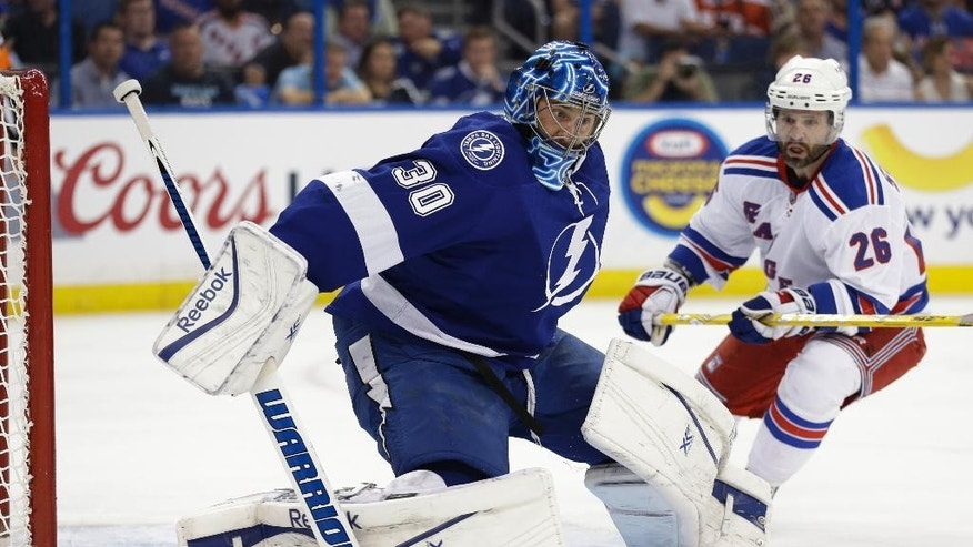 Tampa Bay Lightning goalie Ben Bishop (30) turns away a shot as New York Rangers right wing Martin St. Louis (26) looks for a rebound, during the first period of Game 3 of the Eastern Conference finals in the NHL hockey Stanley Cup playoffs Wednesday, May 20, 2015, in Tampa, Fla. (AP Photo/Chris O'Meara)