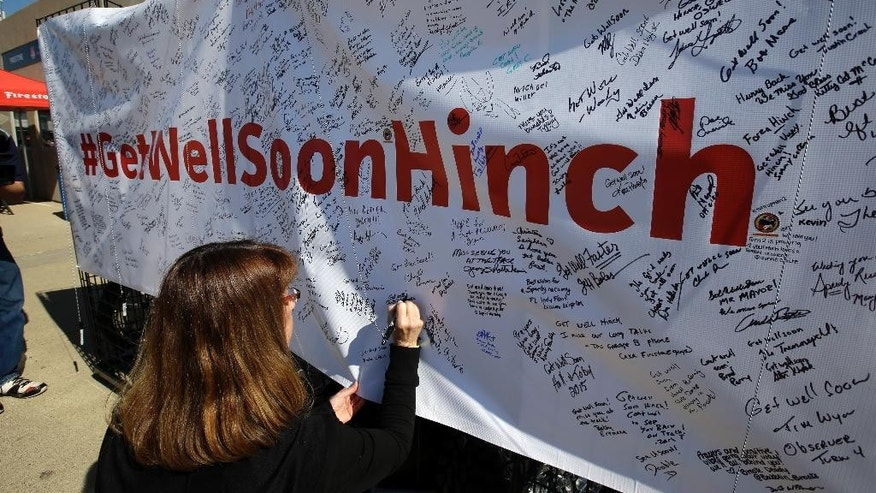 """Deb Sparks signs a """"Get Well Soon Hinch"""" banner in the garage area before the practice session for the Indianapolis 500 auto race at Indianapolis Motor Speedway in Indianapolis, Friday, May 22, 2015. James Hinchcliffe, of Canada, was injured in a crash on Monday and is being replaced by Ryan Briscoe, of Australia. (AP Photo/Darron Cummings)"""
