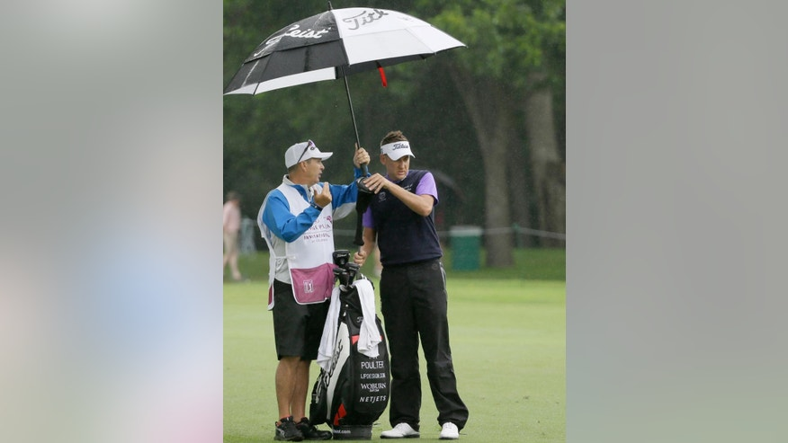 Ian Poulter, right, listens to his caddie Terry Mundy while under an umbrella before an approach shot on the ninth hole during the second round of the Colonial golf tournament, Friday, May 22, 2015, in Fort Worth, Texas. (AP Photo/LM Otero)