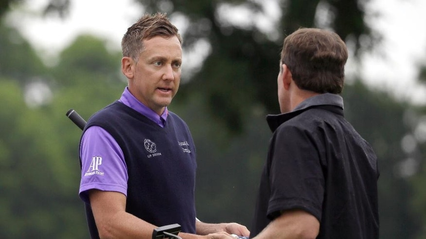 Ian Poulter, left, shakes hands with Justin Leonard after they finished their second round of the Colonial golf tournament, Friday, May 22, 2015, in Fort Worth, Texas. (AP Photo/LM Otero)