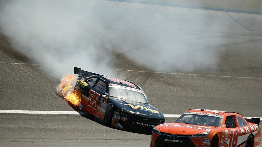 Flames shoot from Jamie Dick's car after he hit the wall during the NASCAR Xfinity series auto race at Charlotte Motor Speedway in Concord, N.C., on Saturday, May 23, 2015. (AP Photo/Chris Keane)