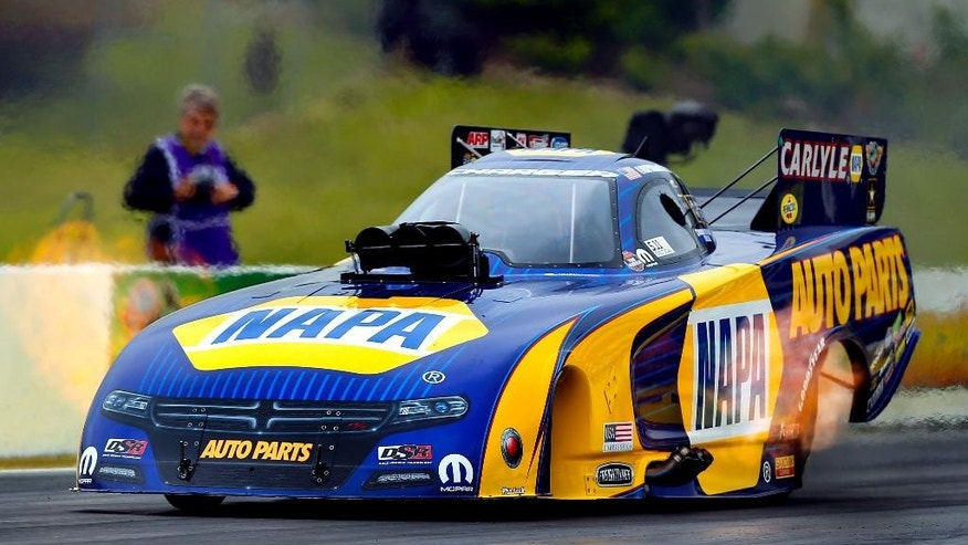 Flames shoot out of the side of Ron Capp's Funny Car as he tears down the track during the NHRA Kansas Nationals, Saturday, May 23, 2015, at Heartland Park in Topeka, Kan. (Chris Neal/The Topeka Capital-Journal via AP)