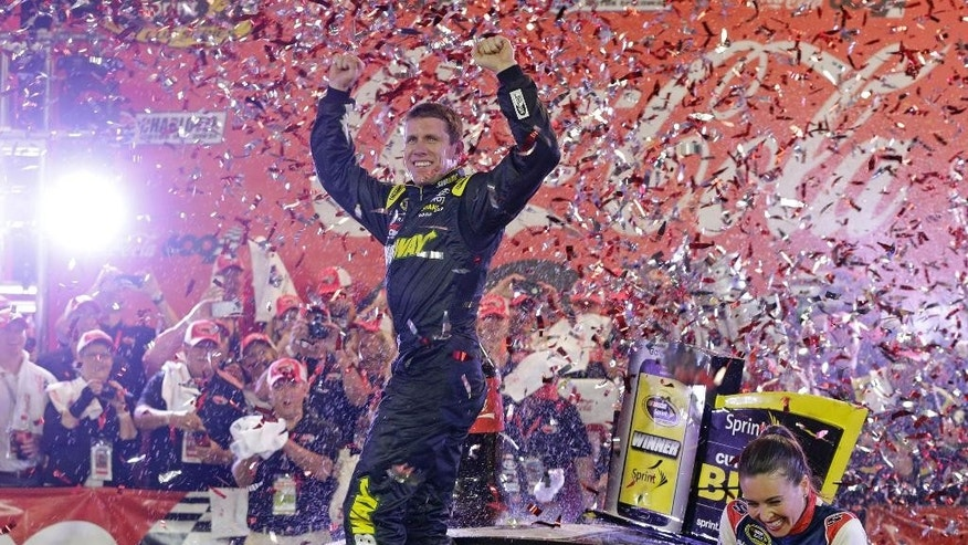Carl Edwards celebrates in Victory Lane after winning the NASCAR Sprint Cup series auto race at Charlotte Motor Speedway in Concord, N.C., Sunday, May 24, 2015. (AP Photo/Chuck Burton)