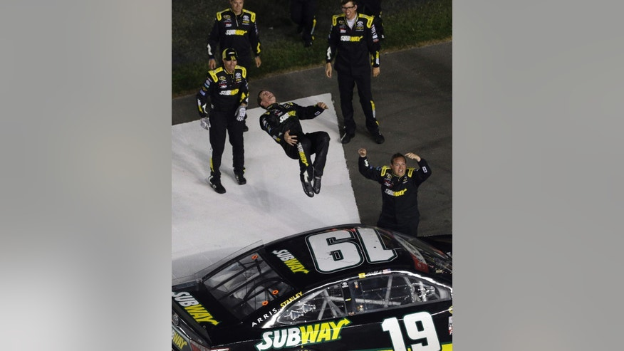 Carl Edwards does a back flip from his car after winning the NASCAR Sprint Cup series auto race at Charlotte Motor Speedway in Concord, N.C., Sunday, May 24, 2015. (AP Photo/Gerry Broome)