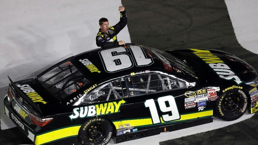 Carl Edwards celebrates after winning the NASCAR Sprint Cup series auto race at Charlotte Motor Speedway in Concord, N.C., Sunday, May 24, 2015. (AP Photo/Gerry Broome)